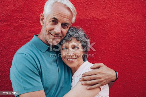 529076288 istock photo Loving middle aged couple embracing 529077352