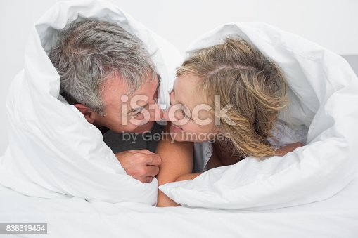 istock Loving middle aged couple under the duvet 836319454