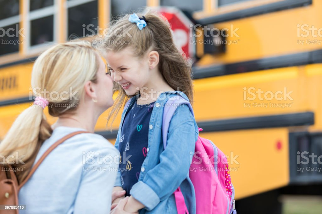 Loving mom sends adorable daughter off to school stock photo