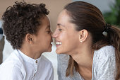 Loving mother and African American little son touching noses close up, expressing love, smiling mom and adorable child enjoying funny moment, free time together, playing, family having fun