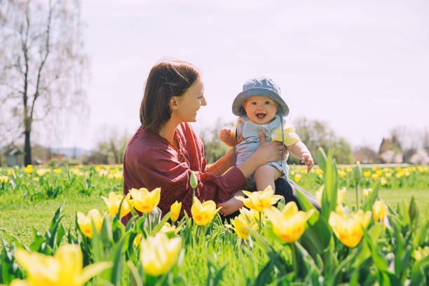 Amante de la madre y la niña entre las flores de tulipanes amarillos. - foto de stock