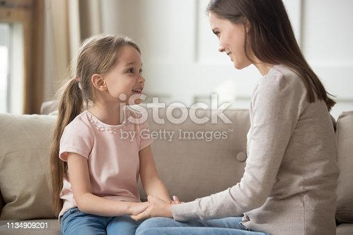 istock Loving mother and child holding hands talking sitting on sofa 1134909201
