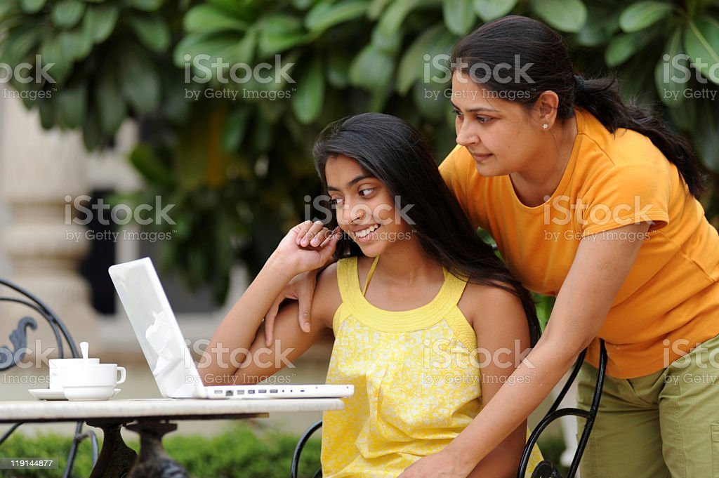 Loving mother and daughter using laptop together outdoors stock photo