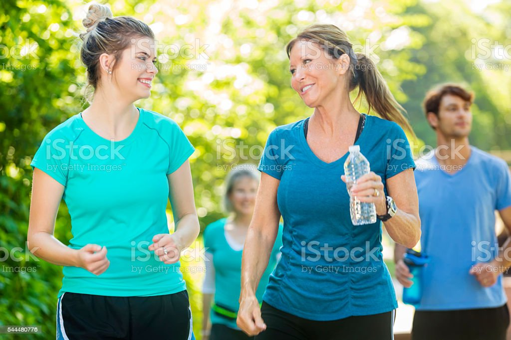 Loving mother and daughter walking together stock photo