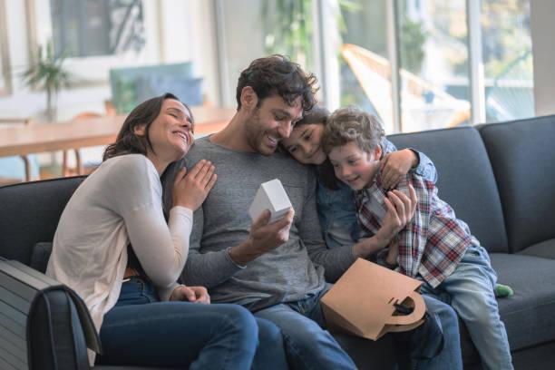 matriz loving e miúdos que comemoram o pai, dia de abraço do paizinho quando abre um presente todo o sorriso - feliz dia dos pais - fotografias e filmes do acervo