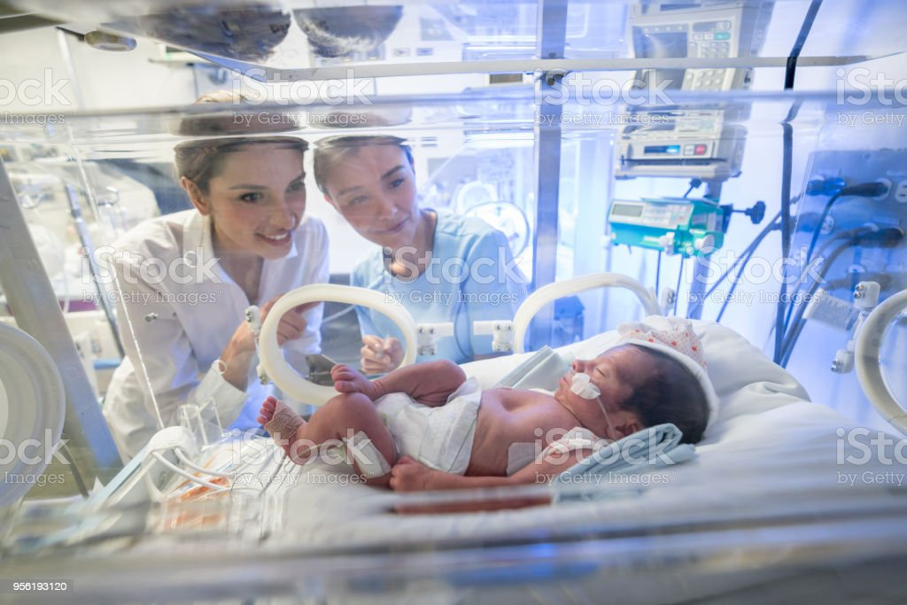 Loving Mother And Nurse At Neonatal Intensive Care Unit Looking At