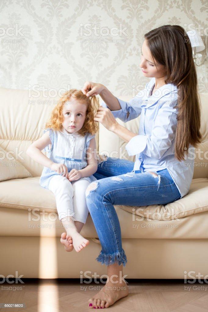 Loving mother braiding hair of her little daughter stock photo