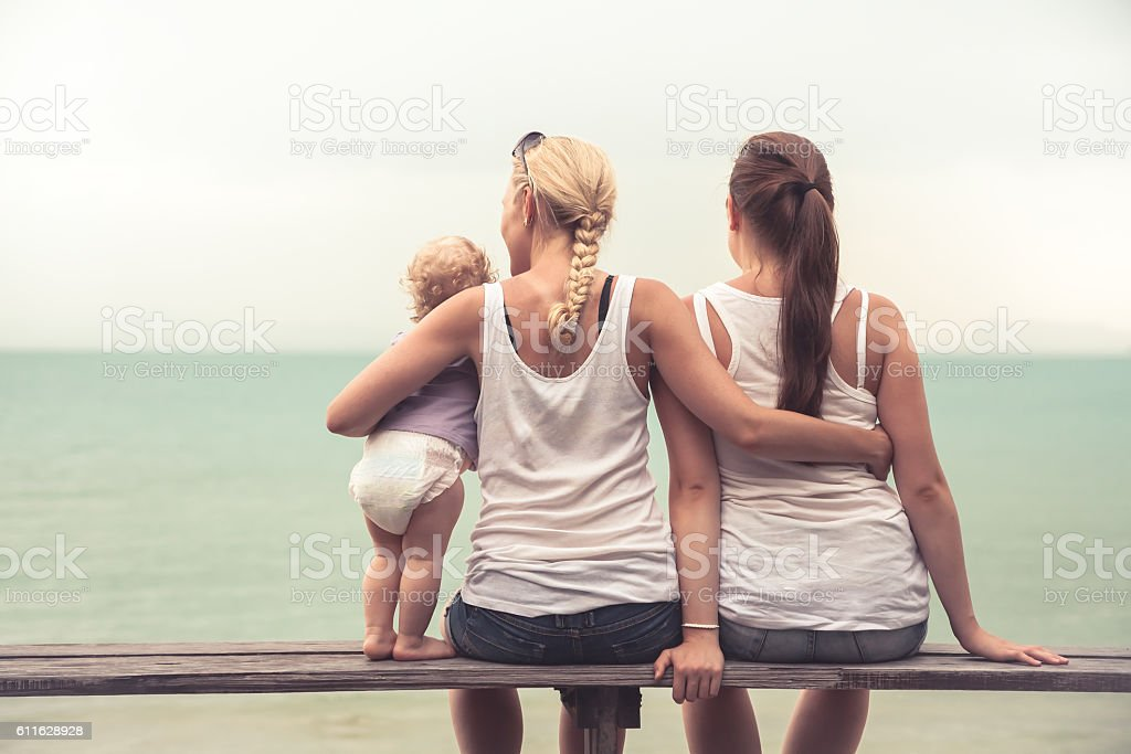 Loving mother embracing her children looking into the distance stock photo