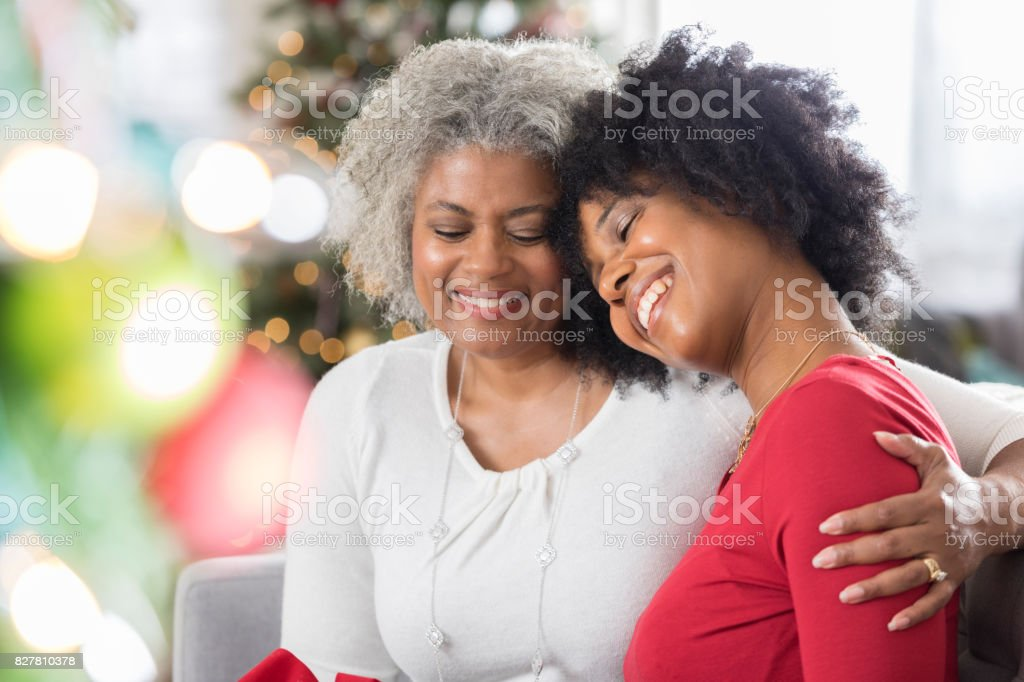 Loving mother enjoys spending time with adult daughter at Christmastime stock photo