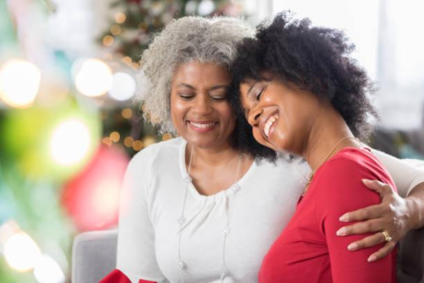 liebevolle mutter verbringt gerne zeit mit erwachsenen tochter zu weihnachten - geschenke eltern weihnachten stock-fotos und bilder