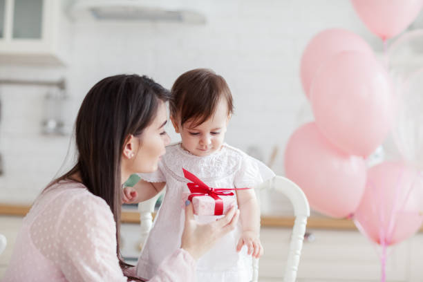 Loving mother giving birthday present to her cute baby daughter and telling her warm wishes Loving mother giving birthday present to her cute baby daughter and telling her warm wishes birthday wishes for daughter stock pictures, royalty-free photos & images