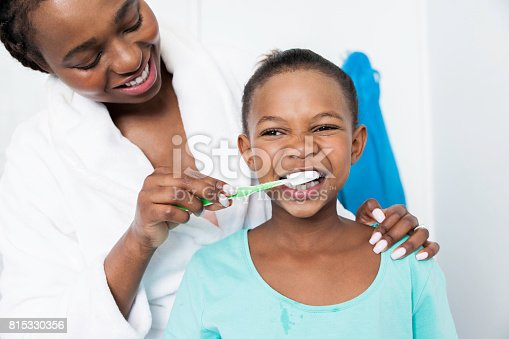 istock Loving mother helping her beautiful daughter brush her teeth. 815330356