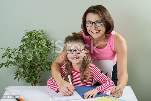 istock Loving mother helping her daughter elementary school pupil  writ 981652286