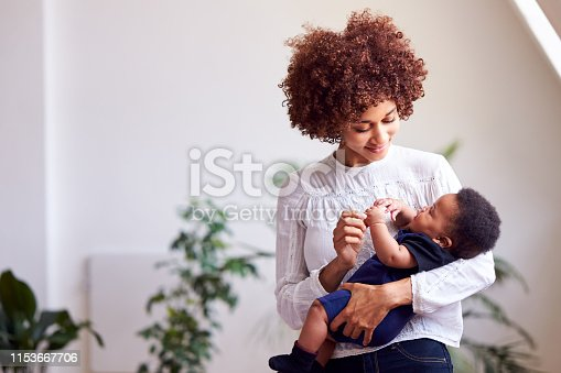 istock Loving Mother Holding Newborn Baby At Home In Loft Apartment 1153667706