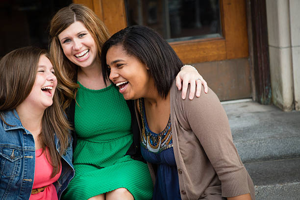 Loving Mother Laughing with Biological and Adopted Daughters stock photo
