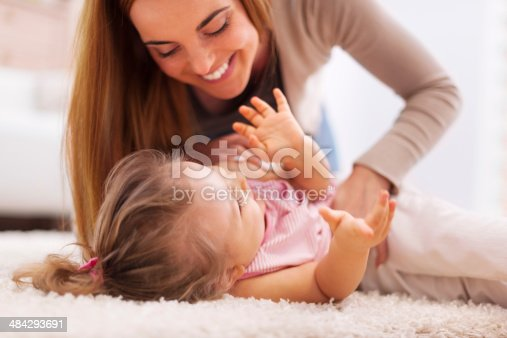 istock Loving mother playing with little girl on carpet 484293691