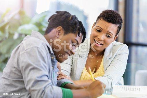 1051247474 istock photo Loving mother praises teenage son's homework diligence 1051247474