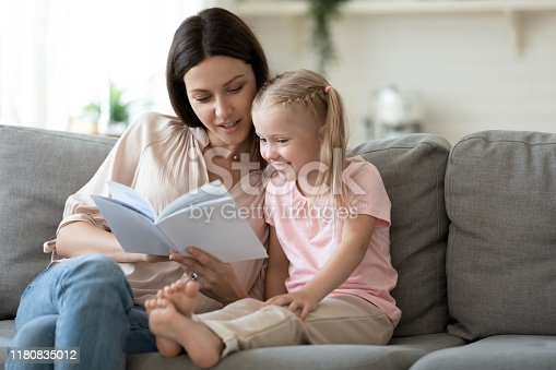 1070262182 istock photo Loving mother teaching little daughter to read at home 1180835012