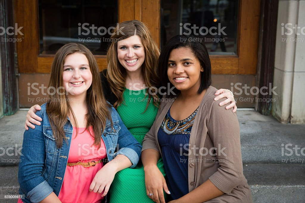Loving Mother with Biological and Adopted Daughters stock photo