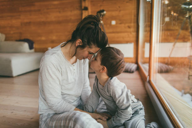 Loving my son Photo of young mother bonding with her son in a log cabin during winter holidays Mother Nature stock pictures, royalty-free photos & images