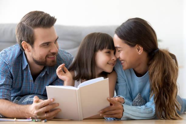 liebevolle eltern genießen entspannendes lesen mit kleiner tochter - die wahrheit tut weh stock-fotos und bilder