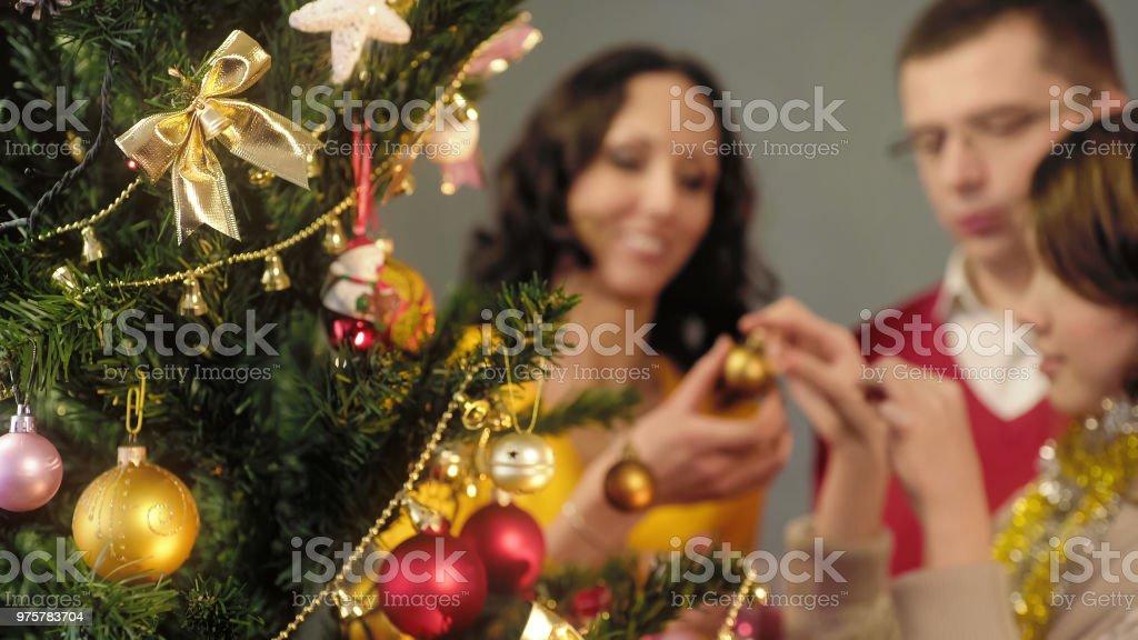 Liebenden Eltern helfen, ihre Tochter zu dekorieren Weihnachtsbaum, magische Momente - Lizenzfrei Baum Stock-Foto