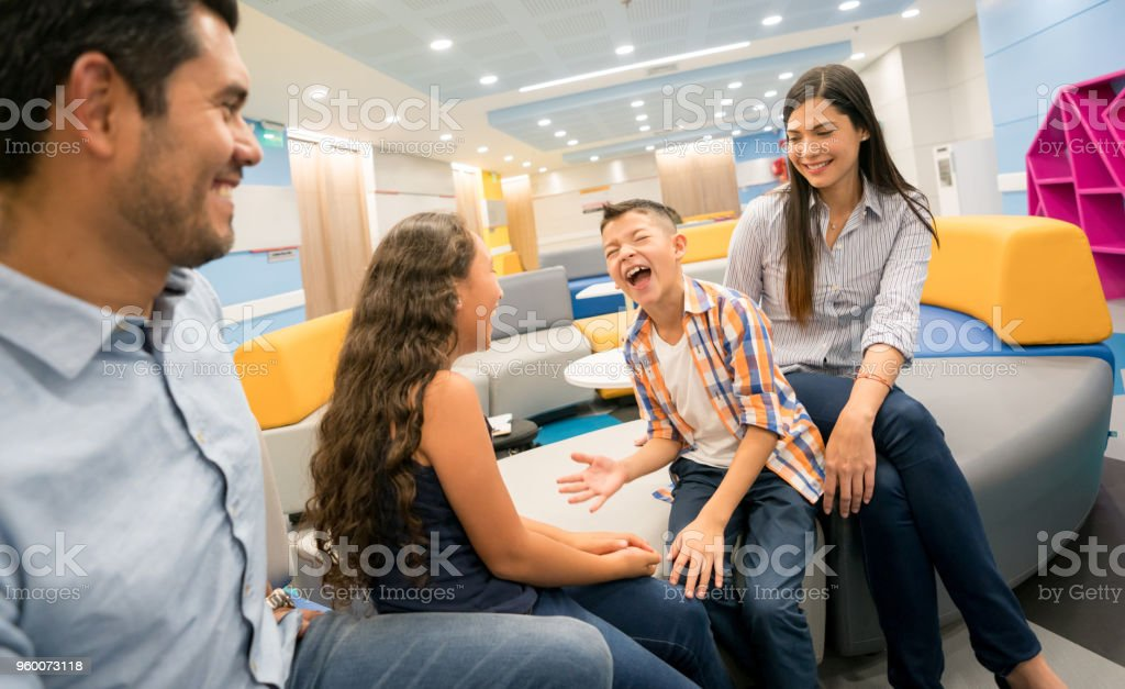 Loving parents looking at their children play and have fun while sitting at the waiting room in a hospital stock photo