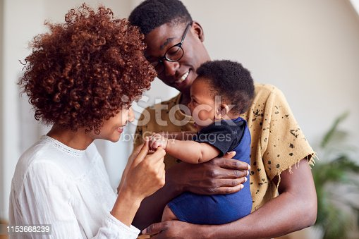 istock Loving Parents Playing With Newborn Baby At Home In Loft Apartment 1153668239