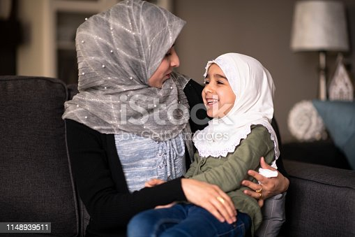 A Muslim mother is smiling while sitting on the couch, with her daughter in her lap. They are both wearing headscarves while cuddling each other.