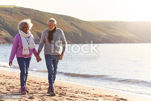 istock Loving Retired Couple Holding Hands As They Walk Along Shoreline On Winter Beach Vacation 1203186030
