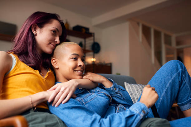 Loving Same Sex Female Couple Lying On Sofa At Home Watching TV And Relaxing Together stock photo