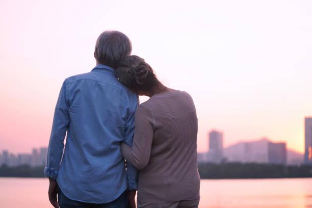 loving senior asian couple watching sunrise stock photo