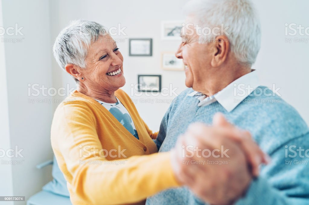 Loving senior couple dancing at home stock photo