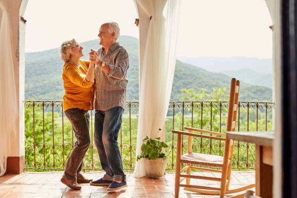 loving senior couple dancing in balcony at home - tipo di danza foto e immagini stock