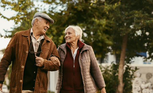 Portrait of happy retired man and woman in warm clothing walking outdoors on street. Loving senior couple enjoy a walk together on a winter day.