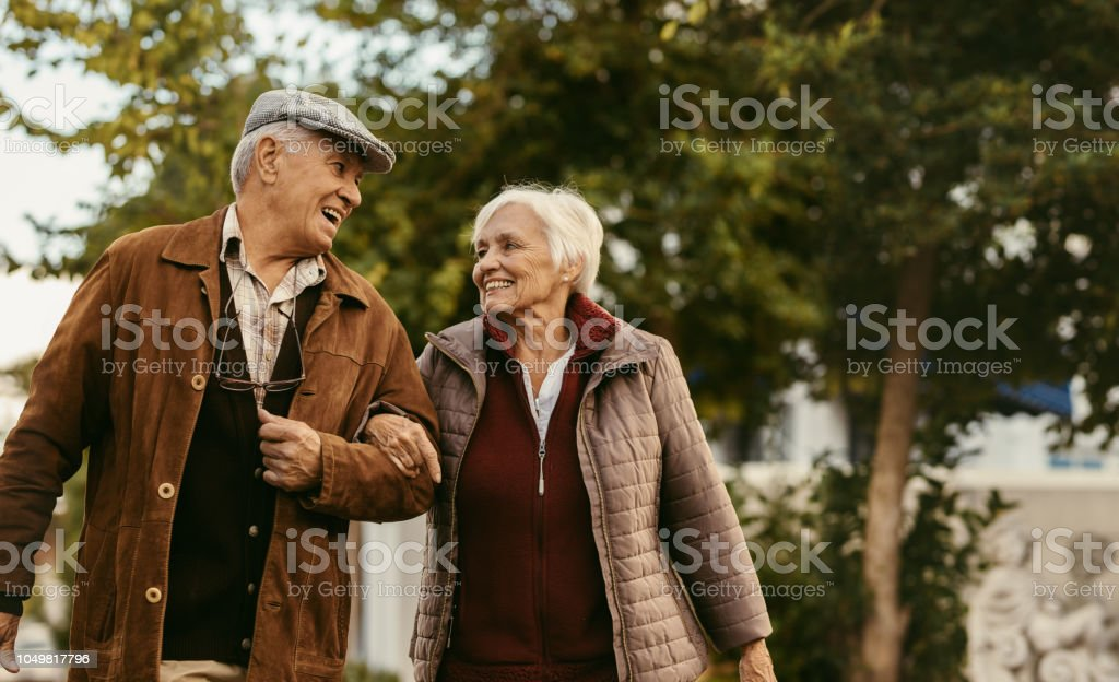Loving senior couple enjoy a walk together on a winter day stock photo