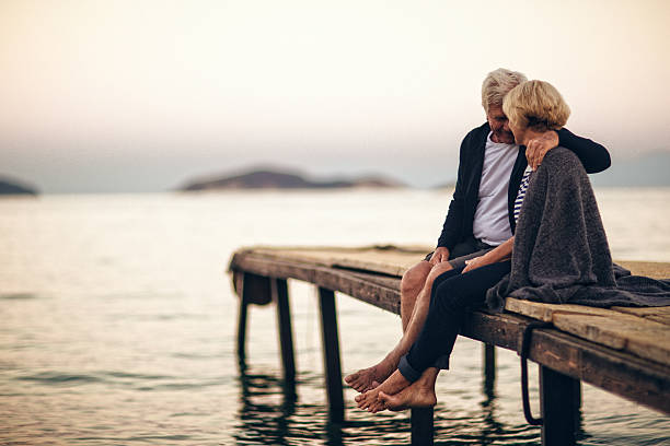 loving senior couple enjoying their life together - pier stock photos and pictures
