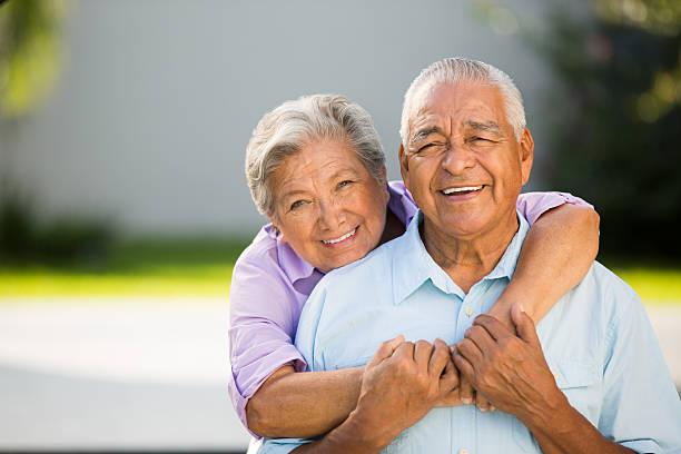 Loving senior couple hugging and posing stock photo