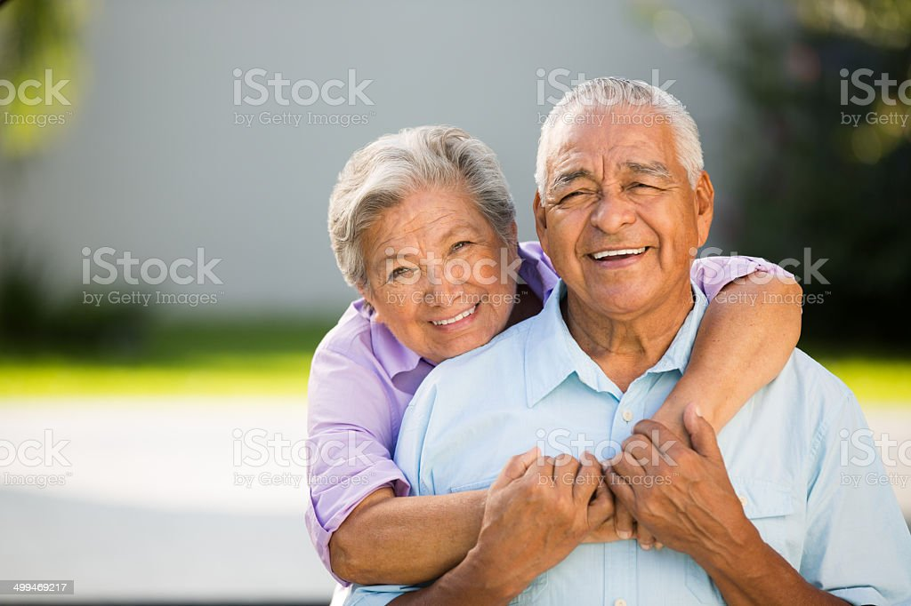 Loving senior couple hugging and posing stock photo