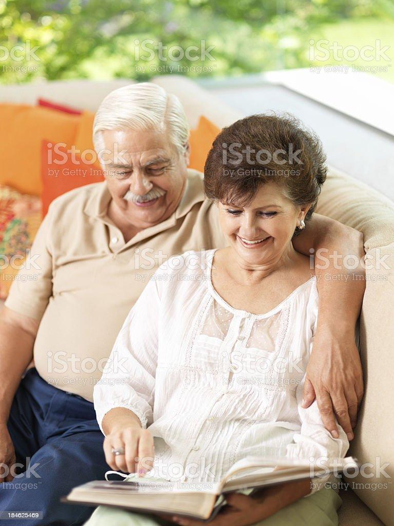 Loving senior couple looking at photo album royalty-free stock photo