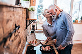 Loving senior couple preparing food at home. Woman is kissing her man.