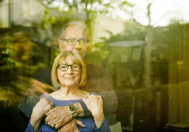 loving senior couple seen through glass window - 60 69 years stock photos and pictures