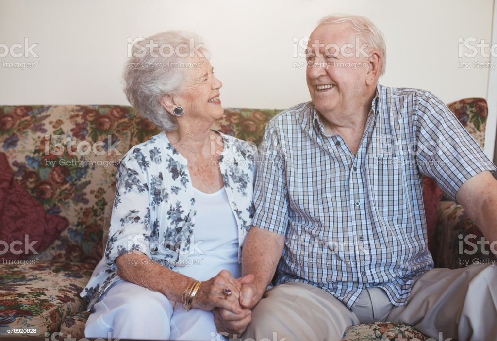 Loving senior couple sitting together at home stock photo