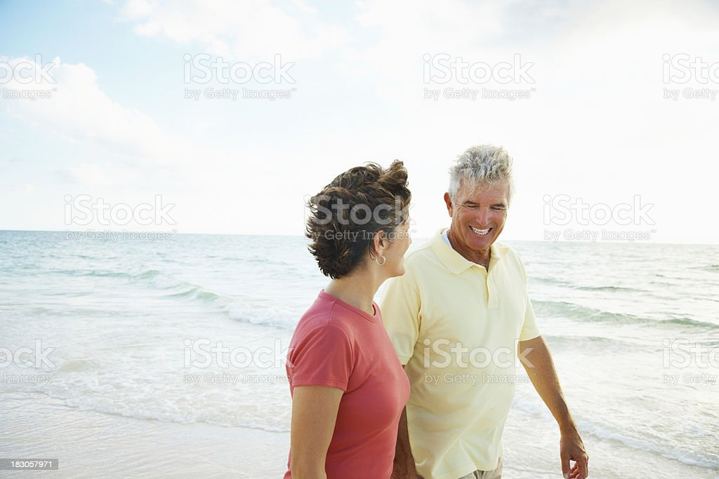 Loving senior couple walking on a scenic beach royalty-free stock photo