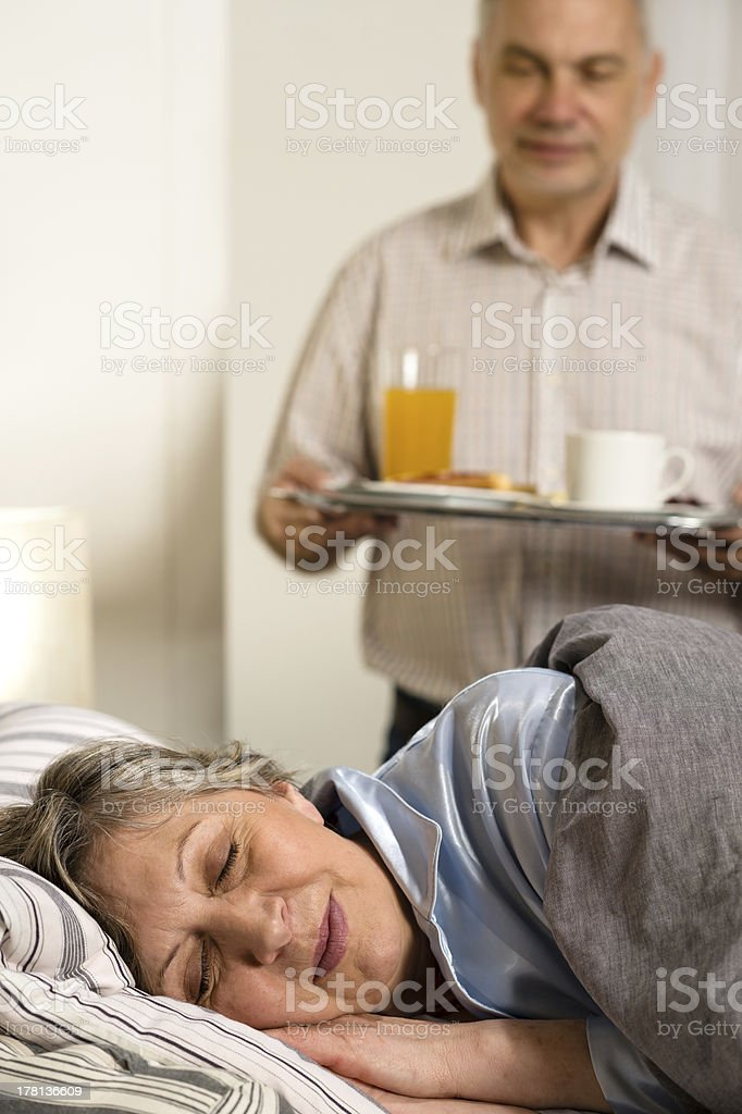 Loving senior husband serving breakfast to wife royalty-free stock photo