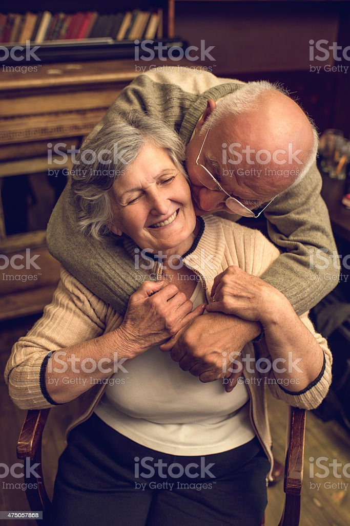 Loving senior man kissing and embracing his wife at home. stock photo