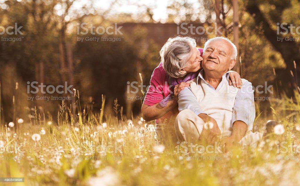 Loving senior woman kissing her husband in grass. stock photo