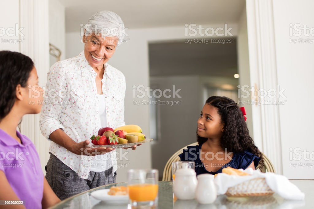 Loving senior woman serving food to granddaughters - Royalty-free 12-13 Years Stock Photo