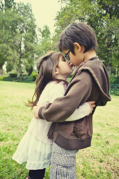 loving siblings giving kiss - little girls little boys kissing love stock photos and pictures