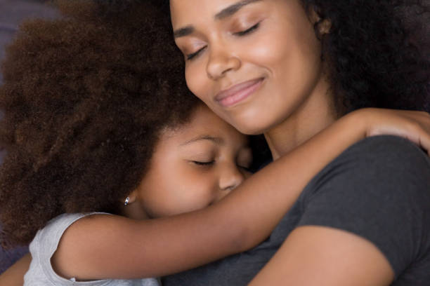 Loving single black mother hugs cute daughter feel tenderness connection stock photo